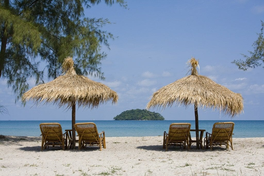 Looking out past a set of beach chairs in the shade of palm umbrellas at Victory Beach, Cambodia.
