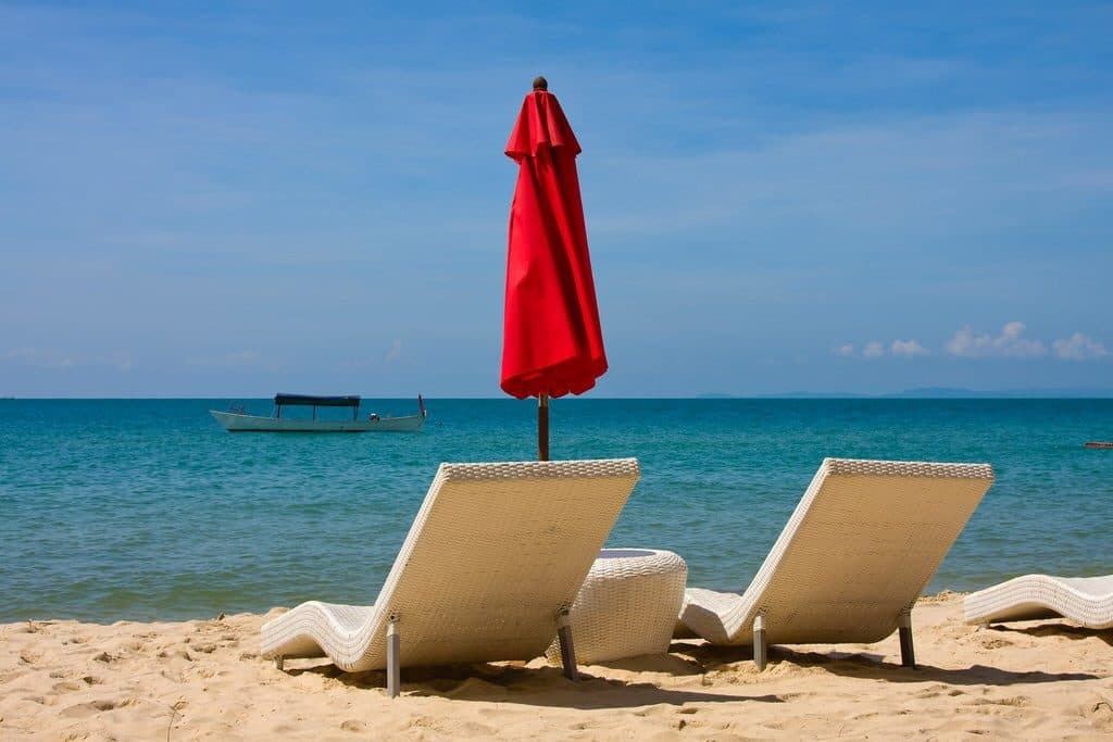 Photo looking out across the beach to the ocean with two wicker beach chairs at Serendipity Beach, Cambodia.